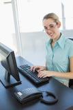 Empresaria tranquila contenta que se sienta en su escritorio que trabaja en el ordenador Imágenes de archivo libres de regalías