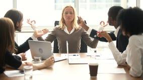 Empresaria tranquila que medita en la reunión con los colegas multirraciales, ninguna tensión