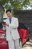 Empresaria Using Cell Phone mientras que se inclina en el coche Foto de archivo libre de regalías