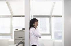 Empresaria Using Cellphone Leaning en la división fotografía de archivo