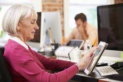 Empresaria Using Digital Tablet en oficina creativa fotos de archivo