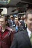 Empresaria Using Mobile Phone en medio de compañeros de trabajo imágenes de archivo libres de regalías
