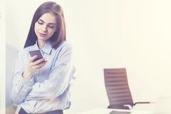 Empresaria Using Mobile Phone en oficina fotografía de archivo libre de regalías