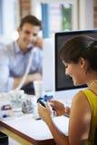 Empresaria Using Mobile Phone en oficina creativa Fotos de archivo libres de regalías