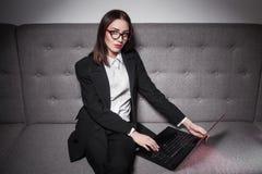 Empresaria vestida en traje y con el ordenador portátil; Fotos de archivo