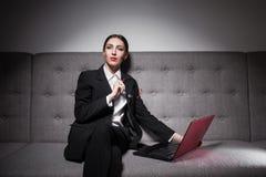 Empresaria vestida en traje y con el ordenador portátil; Imagenes de archivo