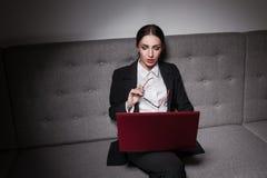 Empresaria vestida en traje y con el ordenador portátil; Imagen de archivo libre de regalías