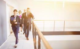 Empresaria Walking On Corridor con los colegas cercando con barandilla adentro foto de archivo