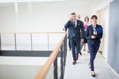 Empresaria Walking On Corridor con los colegas por la verja en oficina fotografía de archivo