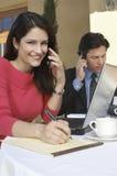 Empresaria Writing While Communicating en el teléfono móvil fotografía de archivo libre de regalías