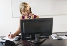 Empresaria Writing On Document mientras que habla en Phon de la línea horizonte imagen de archivo libre de regalías