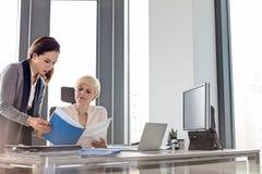 Empresaria y libro de lectura femenino del encargado en el escritorio en oficina foto de archivo