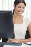 Empresaria y ordenador hispánicos de la mujer en oficina Imagenes de archivo