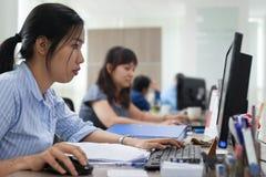 Empresarias asiáticas que trabajan la oficina que se sienta del ordenador imágenes de archivo libres de regalías