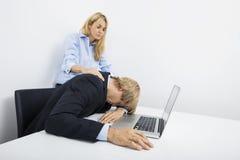 Empresarias con el compañero de trabajo con exceso de trabajo en el escritorio en oficina Imagen de archivo libre de regalías