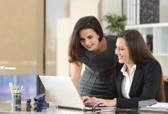 Empresarias coworking con el ordenador portátil en la oficina imágenes de archivo libres de regalías