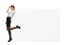 Empresarias en el fondo blanco que se coloca con una pierna aumentada detrás y que se inclina en un letrero blanco grande Imágenes de archivo libres de regalías