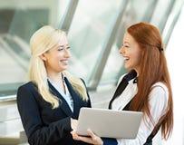 Empresarias felices que sonríen, discutiendo un trato, sosteniendo el ordenador Foto de archivo libre de regalías