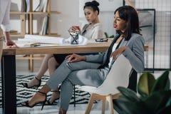 Empresarias jovenes en el desgaste formal que se sienta cerca de la tabla con el modelo Fotos de archivo libres de regalías
