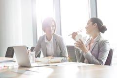 Empresarias jovenes que almuerzan en la tabla en oficina fotografía de archivo libre de regalías