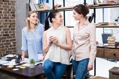 Empresarias jovenes que hablan en el lugar de trabajo mientras que teniendo descanso para tomar café Foto de archivo