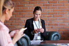 Empresarias jovenes que mandan un SMS en un smartphone Fotografía de archivo libre de regalías