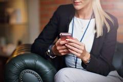 Empresarias jovenes que mandan un SMS en un smartphone Imagen de archivo