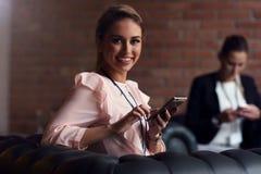 Empresarias jovenes que mandan un SMS en un smartphone Fotografía de archivo