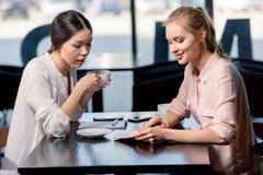 Empresarias jovenes que miran el cuaderno y que discuten proyecto en el descanso para tomar café Imagen de archivo