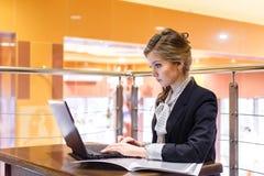 Empresarias jovenes que se sientan en un café y que trabajan en a Foto de archivo libre de regalías