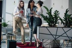 Empresarias jovenes que se unen y que hablan en el descanso para tomar café Fotografía de archivo