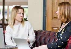 Empresarias jovenes que tienen conversación en la reunión informal Foto de archivo libre de regalías