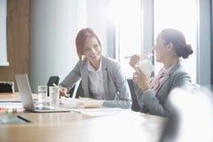 Empresarias jovenes sonrientes que almuerzan en la tabla en oficina Imagen de archivo libre de regalías