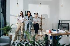 Empresarias jovenes sonrientes que se unen y mirada de la cámara Imagen de archivo libre de regalías
