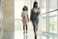 Empresarias que caminan abajo del pasillo de la oficina Fotografía de archivo libre de regalías