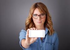 Empresarias que leen el newspaer y que sostienen el móvil Imágenes de archivo libres de regalías