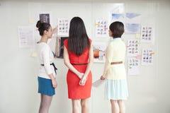 Empresarias que miran la pared de ideas Imágenes de archivo libres de regalías