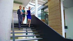 Empresarias que obran recíprocamente con uno a mientras que camina en las escaleras almacen de video