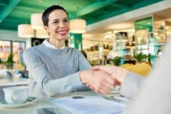 Empresarias que sacuden las manos en la reunión del café imagen de archivo libre de regalías