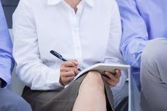 empresarias que toman una nota durante una reunión Foto de archivo libre de regalías