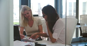 Empresarias que trabajan en los escritorios en oficina abierta moderna del plan almacen de video