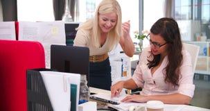 Empresarias que trabajan en los escritorios en oficina abierta moderna del plan almacen de metraje de vídeo