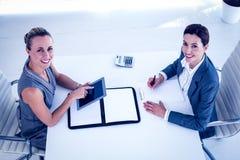 Empresarias que trabajan junto en el escritorio Imagen de archivo