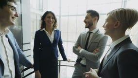 Empresarias y colegas de los hombres de negocios que hablan en elevador móvil y salidos de él en centro de negocios moderno metrajes