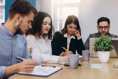 Empresario étnico multi de la gente, concepto de la pequeña empresa Mujer que muestra a compañeros de trabajo algo en el ordenado foto de archivo