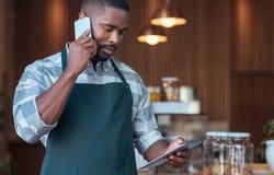 Empresario africano joven difícilmente en el trabajo en su café imágenes de archivo libres de regalías
