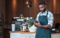 Empresario africano joven que se coloca en su café usando una tableta Imagen de archivo libre de regalías