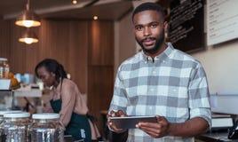 Empresario africano joven que trabaja en el contador de su café Imagenes de archivo