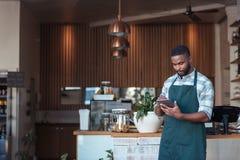 Empresario africano joven que usa una tableta en su café Imagen de archivo