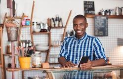 Empresario africano joven sonriente que trabaja en su café foto de archivo libre de regalías